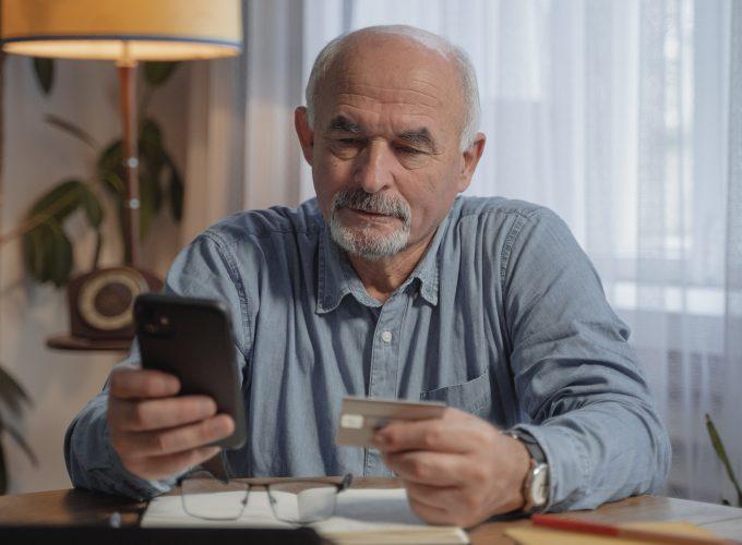 mężczyzna z telefonem i kartą kredytową